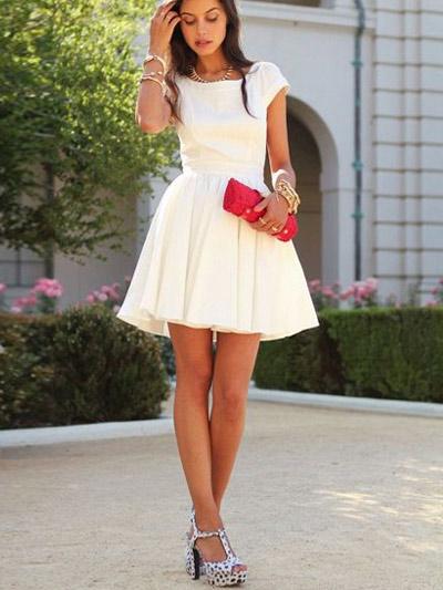 Девушка в белом коротком платье с красным клатчем