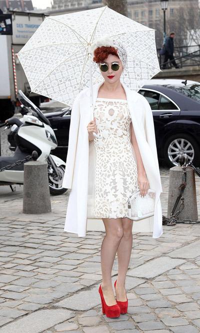 Девушка в белом кружевном платье и красных туфлях на высоких каблуках