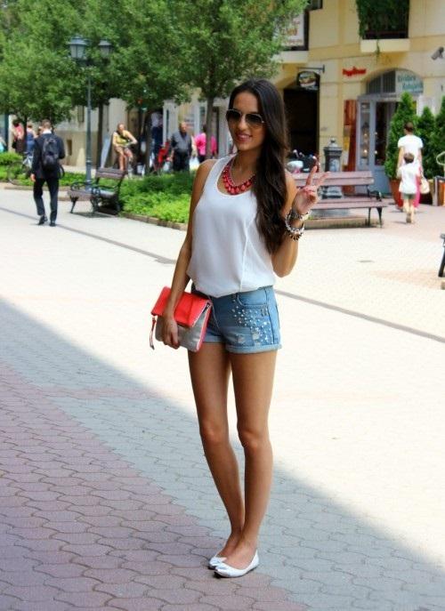 Девушка в белом легком топе и джинсовых шортах