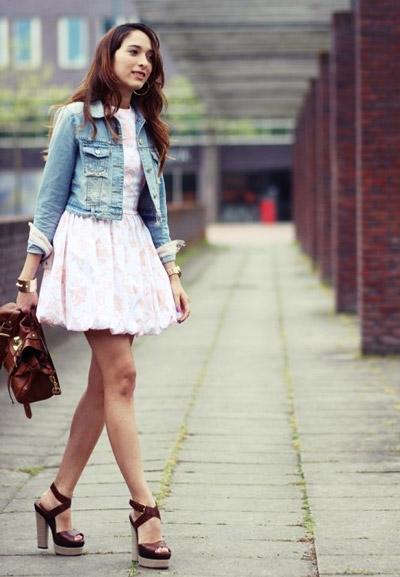 Девушка в белом платье, джинсовке и босоножках на устойчивом каблучке
