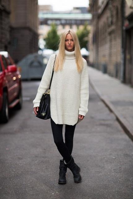 Девушка в белом свитере оверсайз и черных джинсах скинни