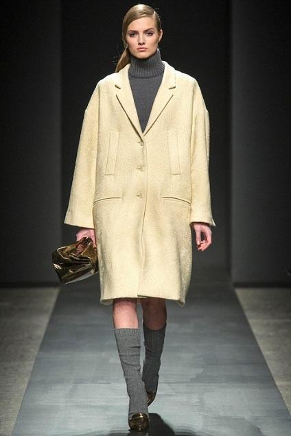 Девушка в бледно-желтом пальто оверсайз и серых гетрах
