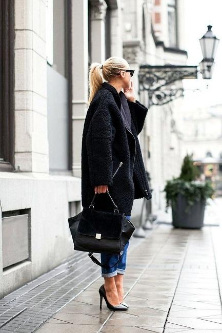 Девушка в черном пальто, джинсах и черных лодочках