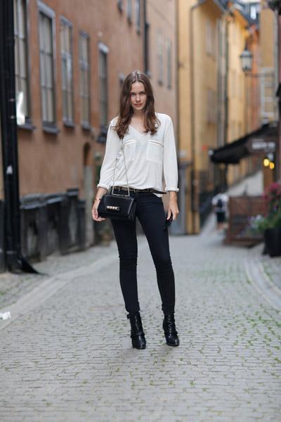 Девушка в черных джинсах и белой блузке