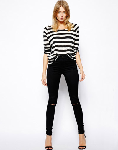 Девушка в черных джинсах скинни с рваными коленками
