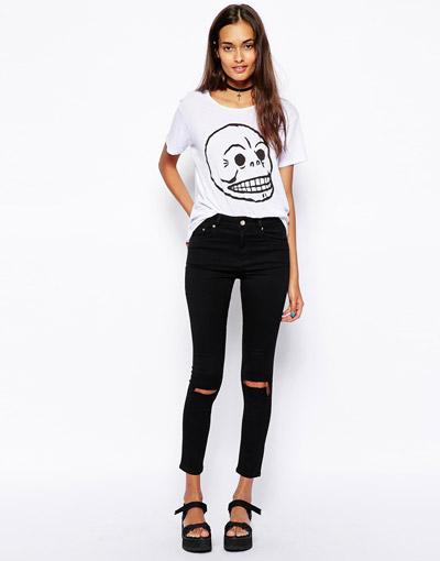Девушка в черных рваных джинсах и белой футболке с принтом