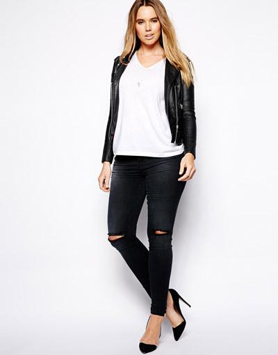 Девушка в черных рваных джинсах и белой футболке