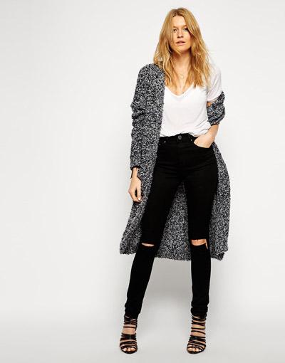 Девушка в черных рваных джинсах и сером пальто