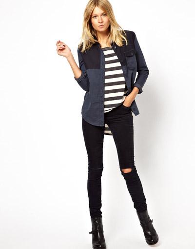 Девушка в черных рваных джинсах и тельняшке