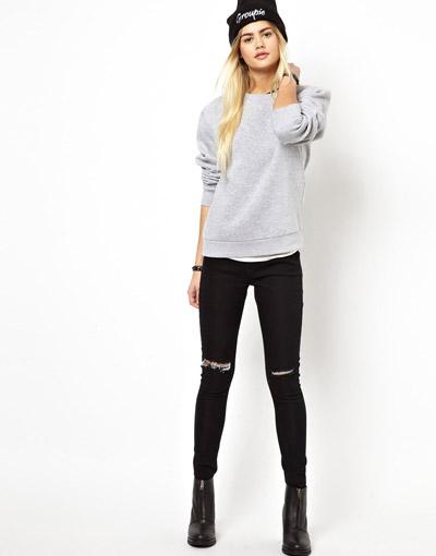 Девушка в джинсах с рваными коленками и сером свитшоте