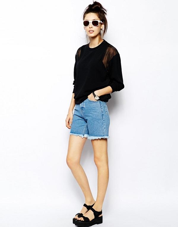 Девушка в джинсовых шортах и черном джемпере