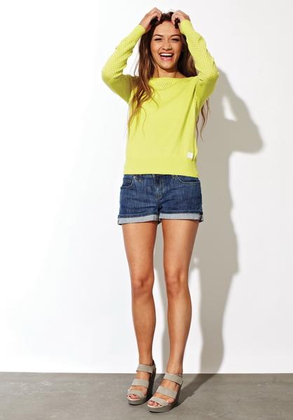 Девушка в джинсовых шортах и желтом джемпере