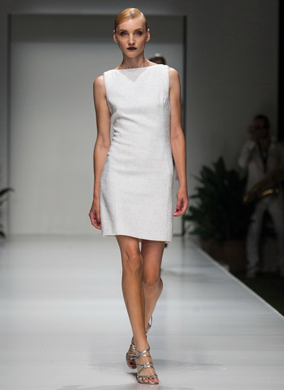 Девушка в коротком белом платье и серебряных босоножках на ремнях
