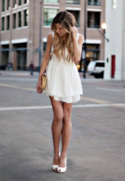 Девушка в коротком белом платье с маленькой сумочкой