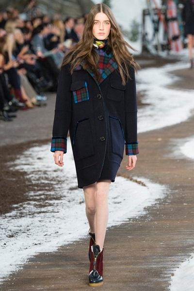Девушка в пальто оверсайз, декорированном клетчатыми вставками на рукавах