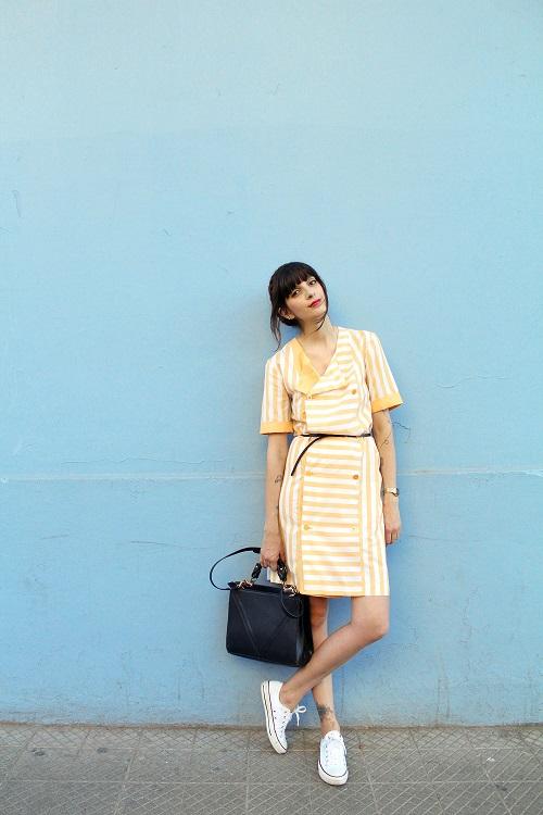 Девушка в платье в желтую полоску и кедах