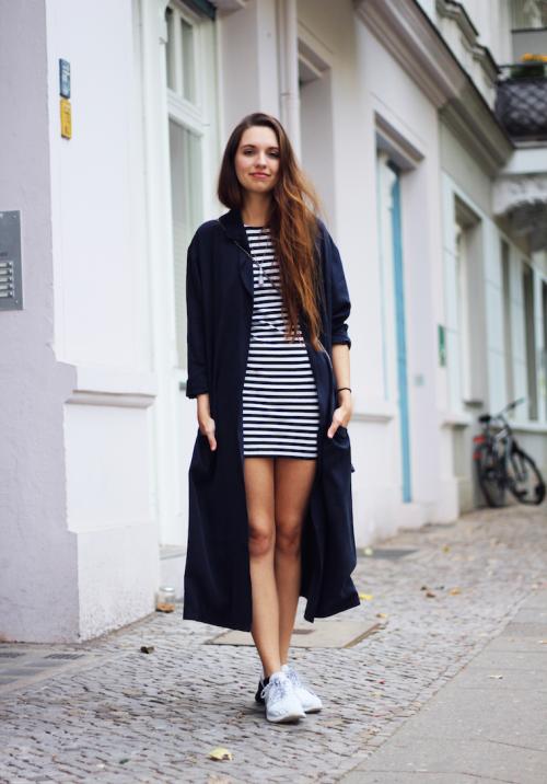 Девушка в полосатом платье, кроссовках и плаще