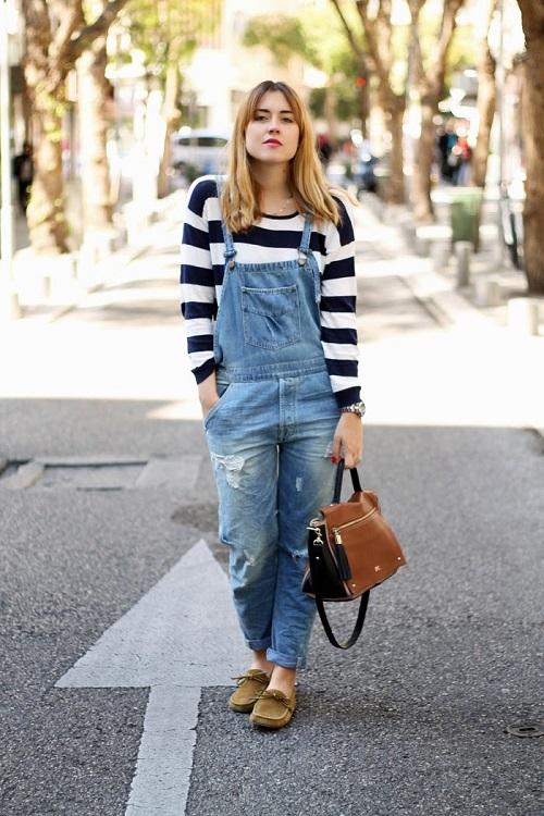 Девушка в полосатом свитшоте и джинсовом комбинезоне