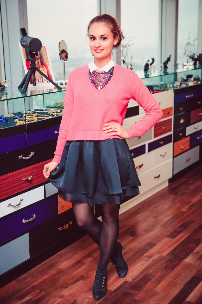 Девушка в розовом джемпере и короткой, широкой юбке