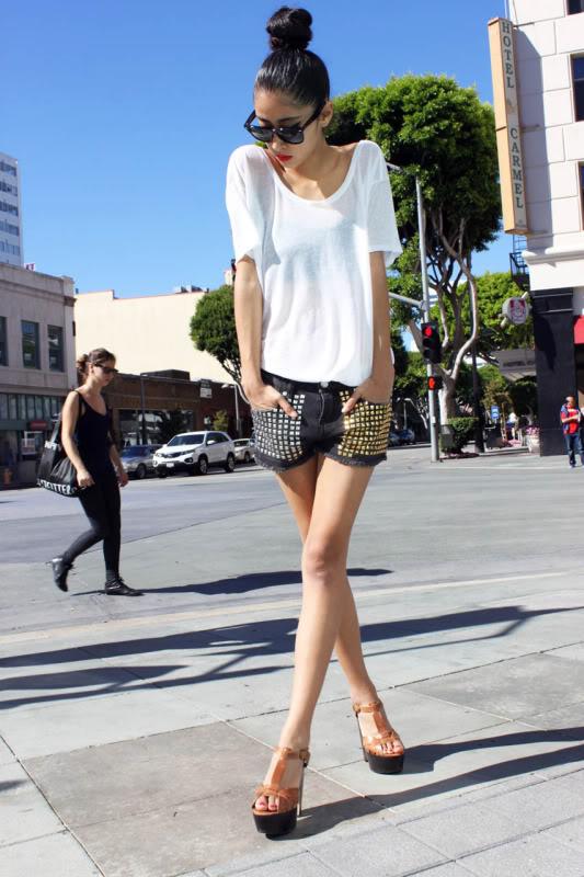 Девушка в шортах с шипами и белой футболке