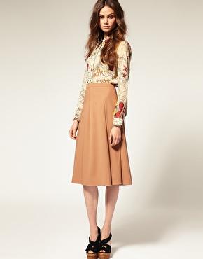 Девушка в юбке миди и блузке с узорами