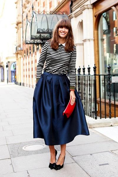 Девушка широкой в юбке миди и полосатой кофте