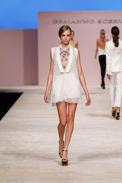 Кара Делевинь в коротком белом платье и золотых босножках