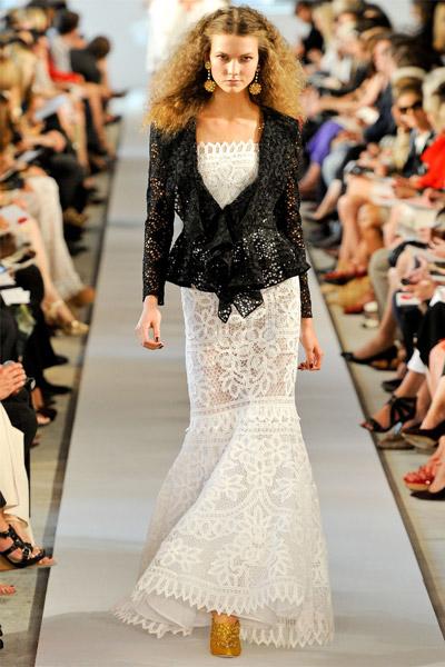 Модель в ажурном белом платье и пиджаке