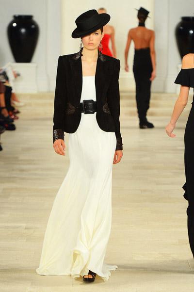 Модель в длинном белом платье и черном пиджаке