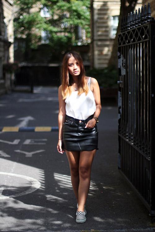 Девушка в кожаной мини юбке, белом топе и слипонах