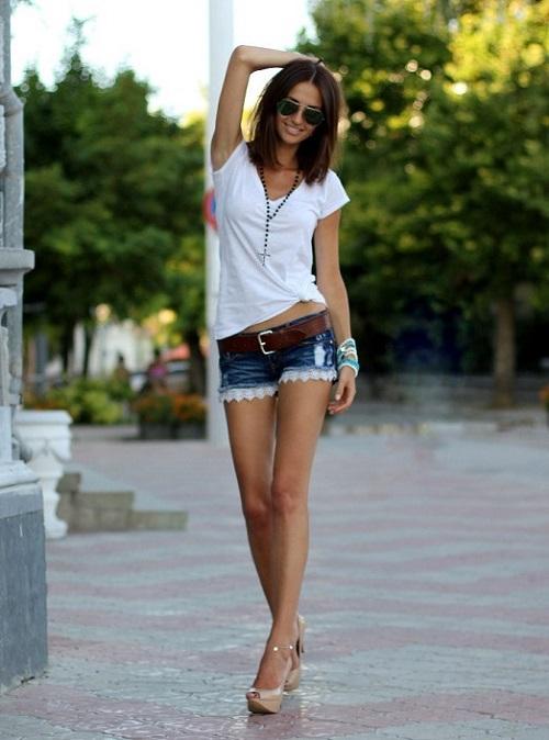 Девушка в белой футболке и джинсовых шортах с ремнем