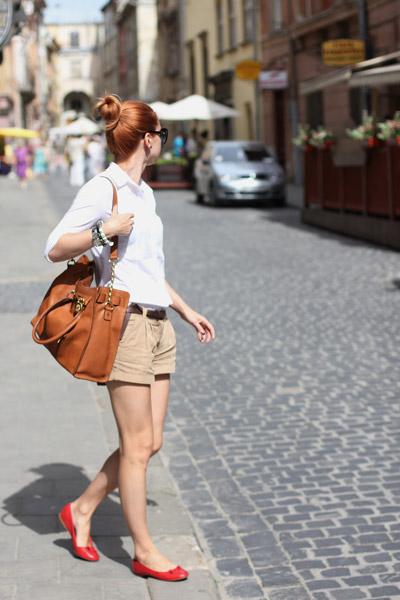 Девушка в бежевых шортах и белой блузке