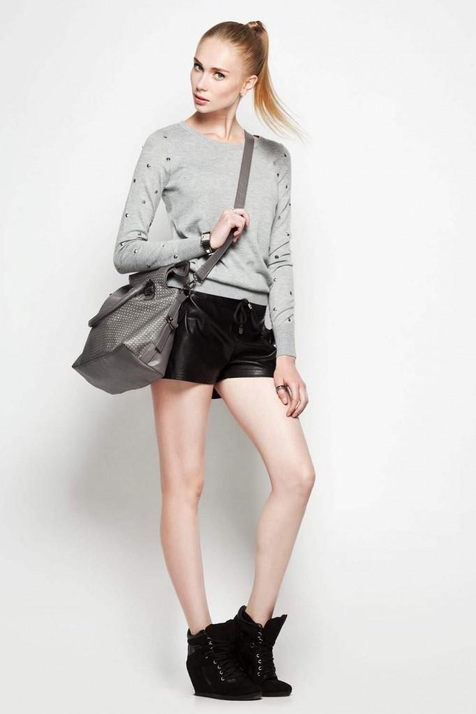 Девушка в черных шортах и сером джемпере