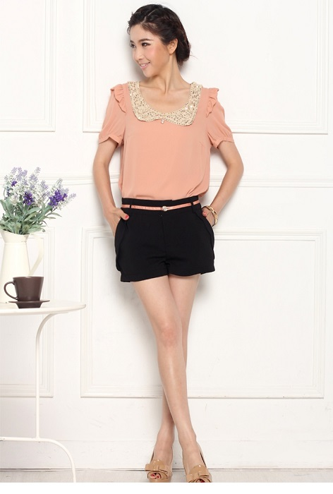 Девушка в черных шортах и светлой персиковой блузке