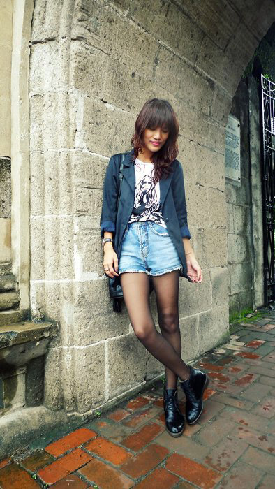 Девушка в джинсовых шортах и темном пиджаке