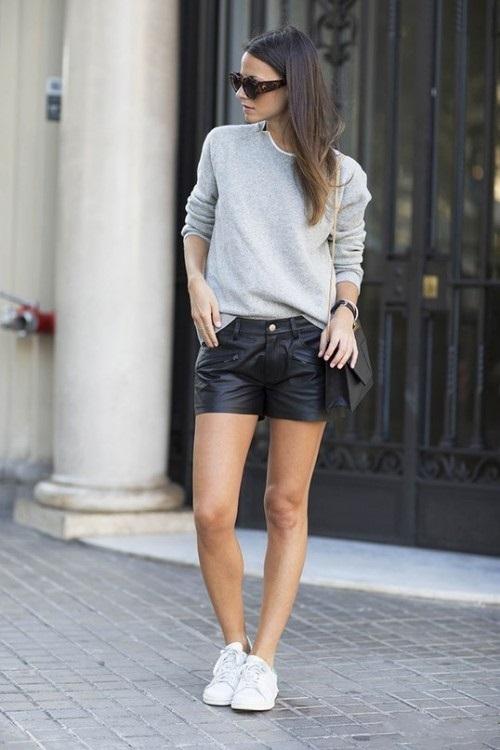 Девушка в кожаных шортах и сером джемпере