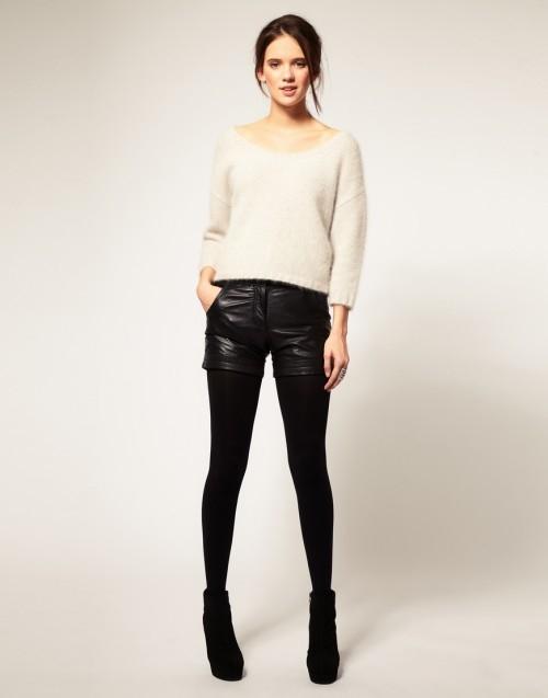 Девушка в кожаных шортах, светлом джемпере и ботильонах