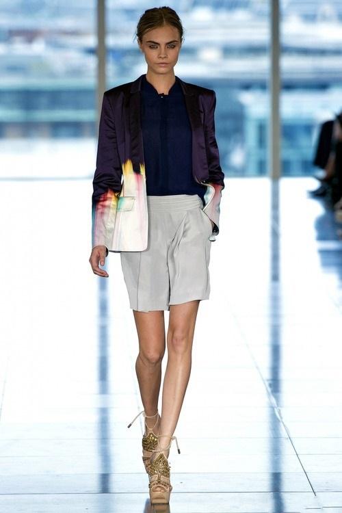 Кара Делевинь в светлых шортах и синей блузке