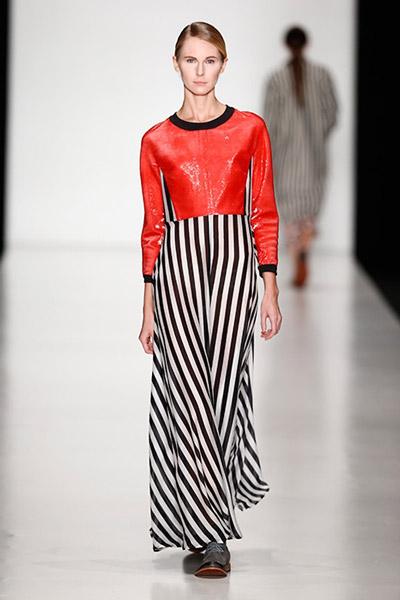 Девушка в юбке в вертикальную полоску и красном свитшоте