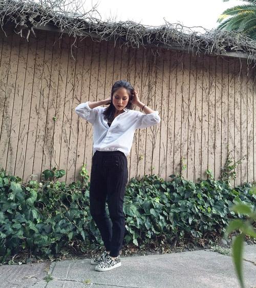 Девушка в черных брюках, белой рубашке и слипонах