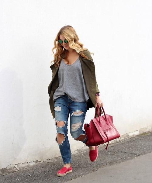 Девушка в рваных джинсах, серой футболке и красных слипонах