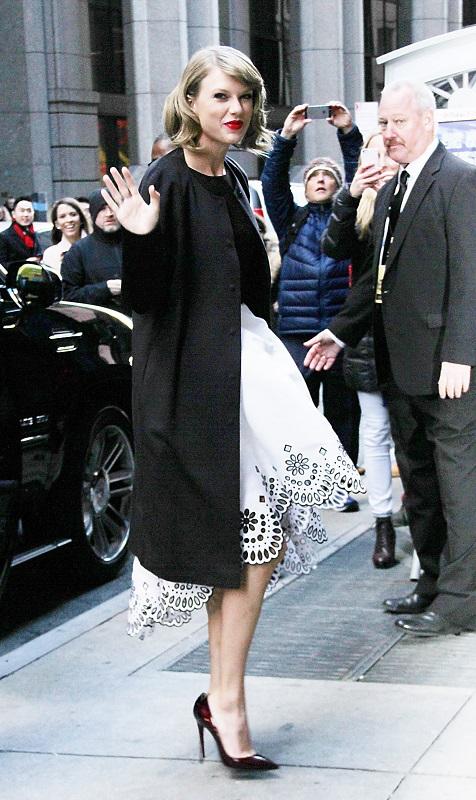 Тейлор Свифт в черном пальто и ассиметричной белой юбке - шикарный лук