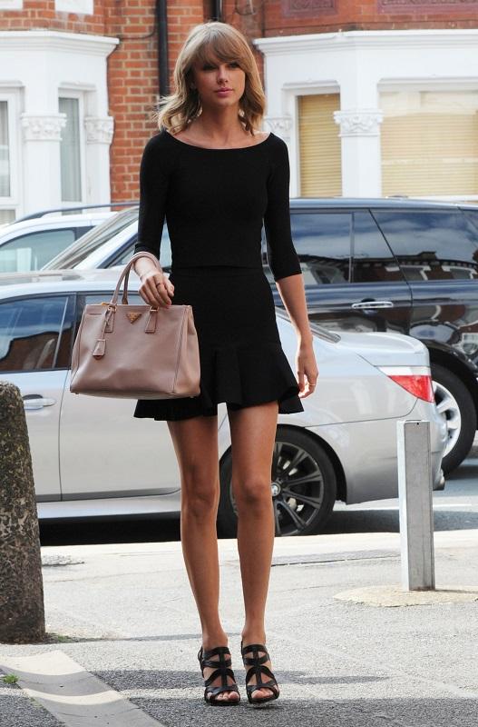 Тейлор Свифт в черной юбке, топе и босоножках
