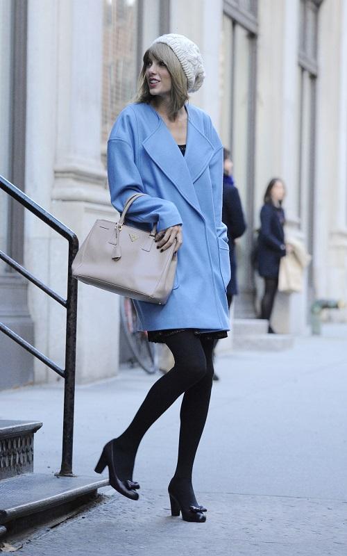 Тейлор Свифт в голубом пальто и белой шапке