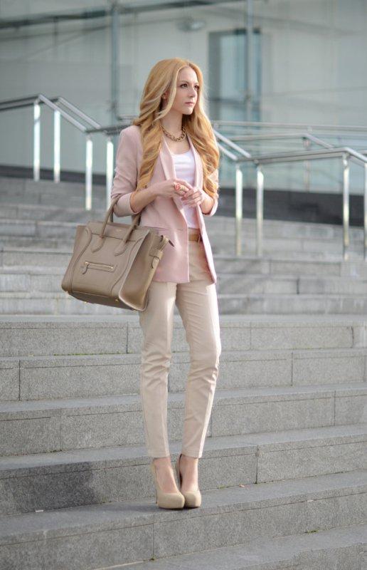 Девушка в бежевых брюках и нежно-розовом пиджаке