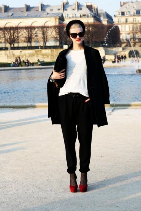 Девушка в черных брюках и красных туфлях на высоком каблуке