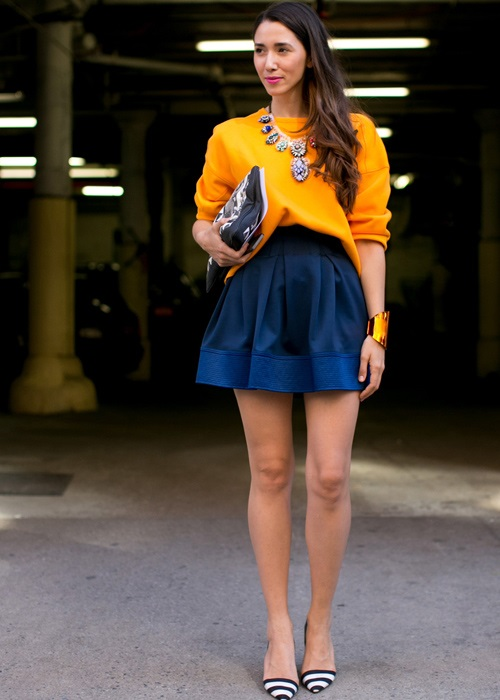 Девушка в короткой темно-синей юбке и оранжевом джемпере