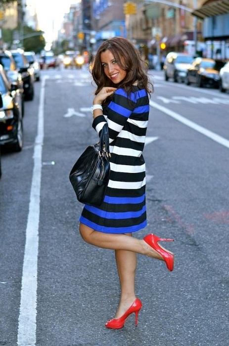 Девушка в полосатом платье и красных туфлях