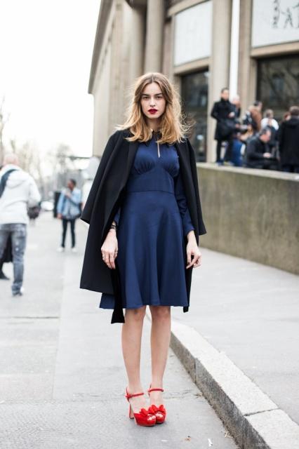 Девушка в темно-синем платье и красных туфлях