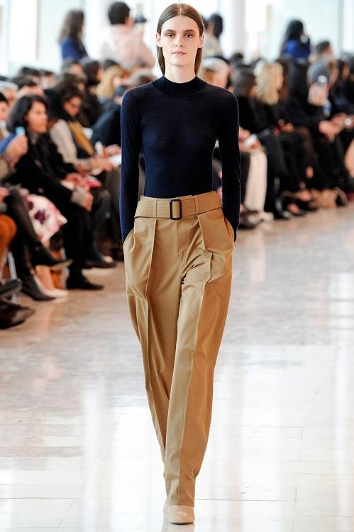 Модель в широких брюках и черной водолазке